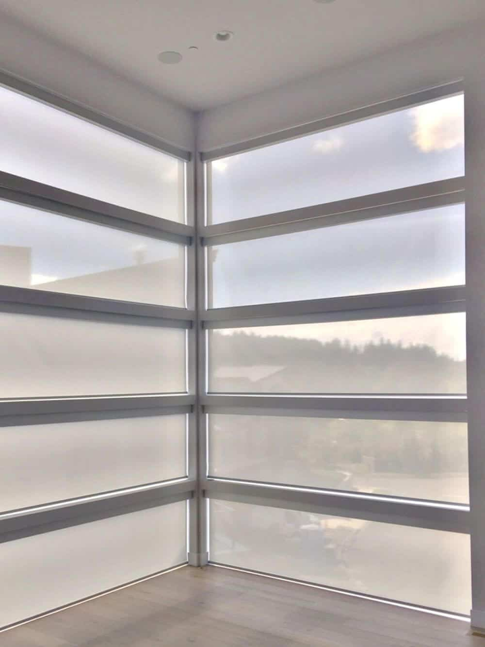 A focused look at this empty modern home's glass windows featuring solar window shades.
