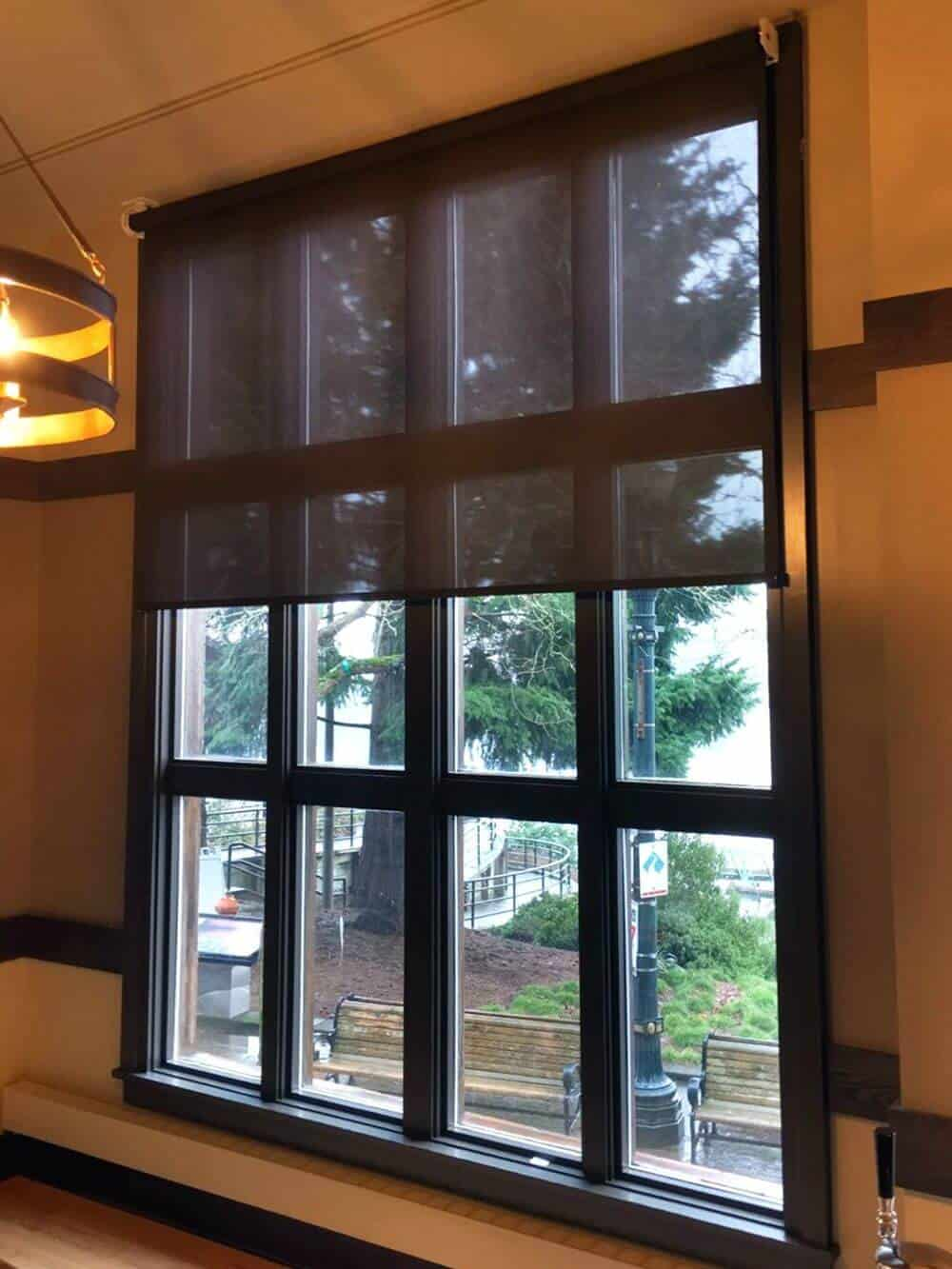 A focused look at this house's windows with gorgeous window frame and has a solar window shade.