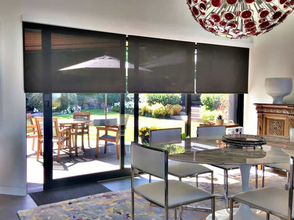 A dining area featuring a large and gorgeous round dining table set lighted by a stunning ceiling light. There's a doorway leading to the outdoor area.