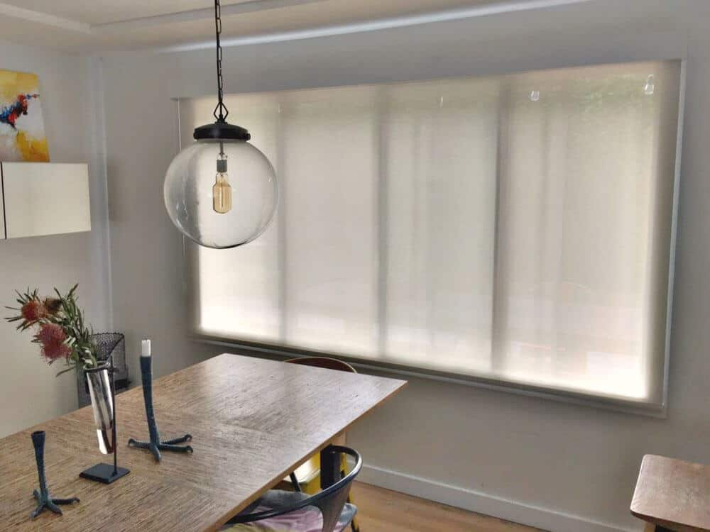 Dining area featuring light gray walls and a tray ceiling, along with hardwood flooring. The room offers a classy rectangular dining table set lighted by pendant lights.