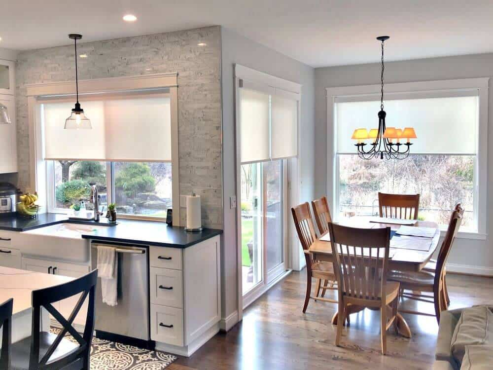 A dine-in kitchen with beautiful backsplash and a black kitchen countertop. There's a center island with a breakfast bar, along with a wooden dining table set lighted by a charming chandelier.