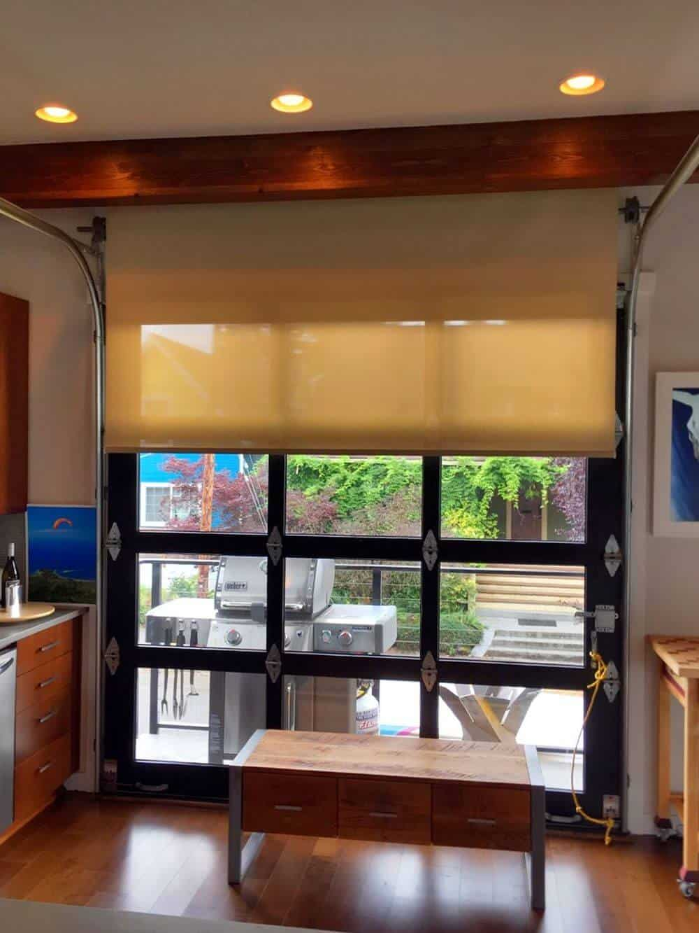 A focused look at this house's gorgeous windows featuring a solar shade. The house also features hardwood floors and a ceiling with exposed beams and has recessed ceiling lights.