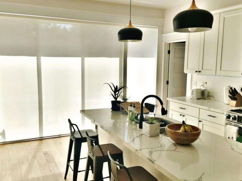 This kitchen features a narrow center island with a marble countertop and has breakfast bar lighted by pendant lights. The area features windows with solar shades.