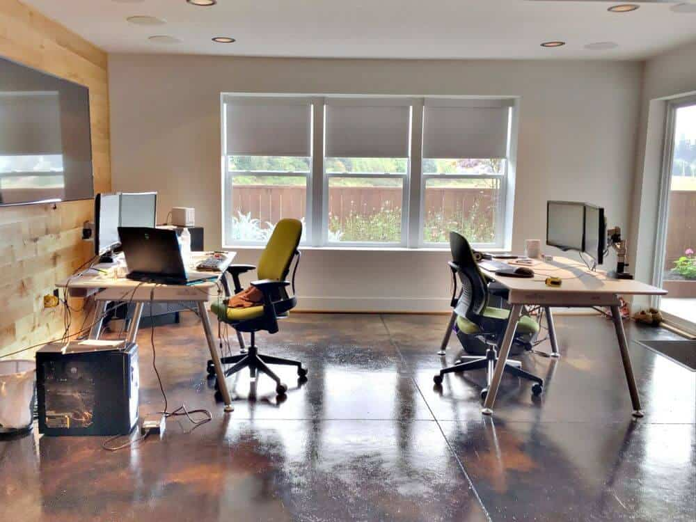 An office area featuring stylish tiles flooring and light gray walls together with a wooden wall. There are two office desks paired with modern chairs, along with a regular ceiling with recessed ceiling lights and glass windows with solar shades.