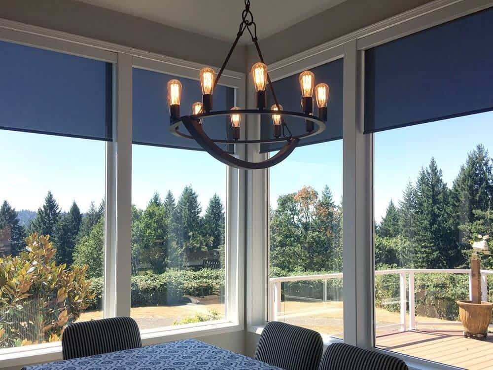 A dining room featuring a stylish dining table and chairs set lighted by a gorgeous chandelier. The room is surrounded by large glass windows featuring solar shades.