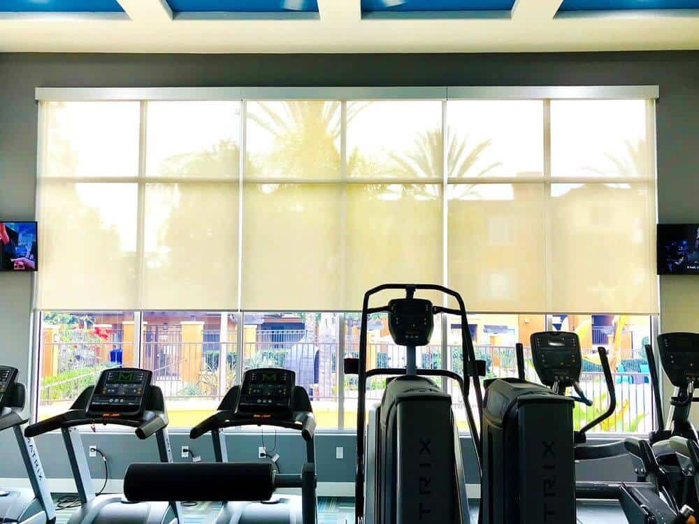 This gym offers high-end equipment and has gray walls and a custom coffered ceiling. The building also has glass windows with solar shades.