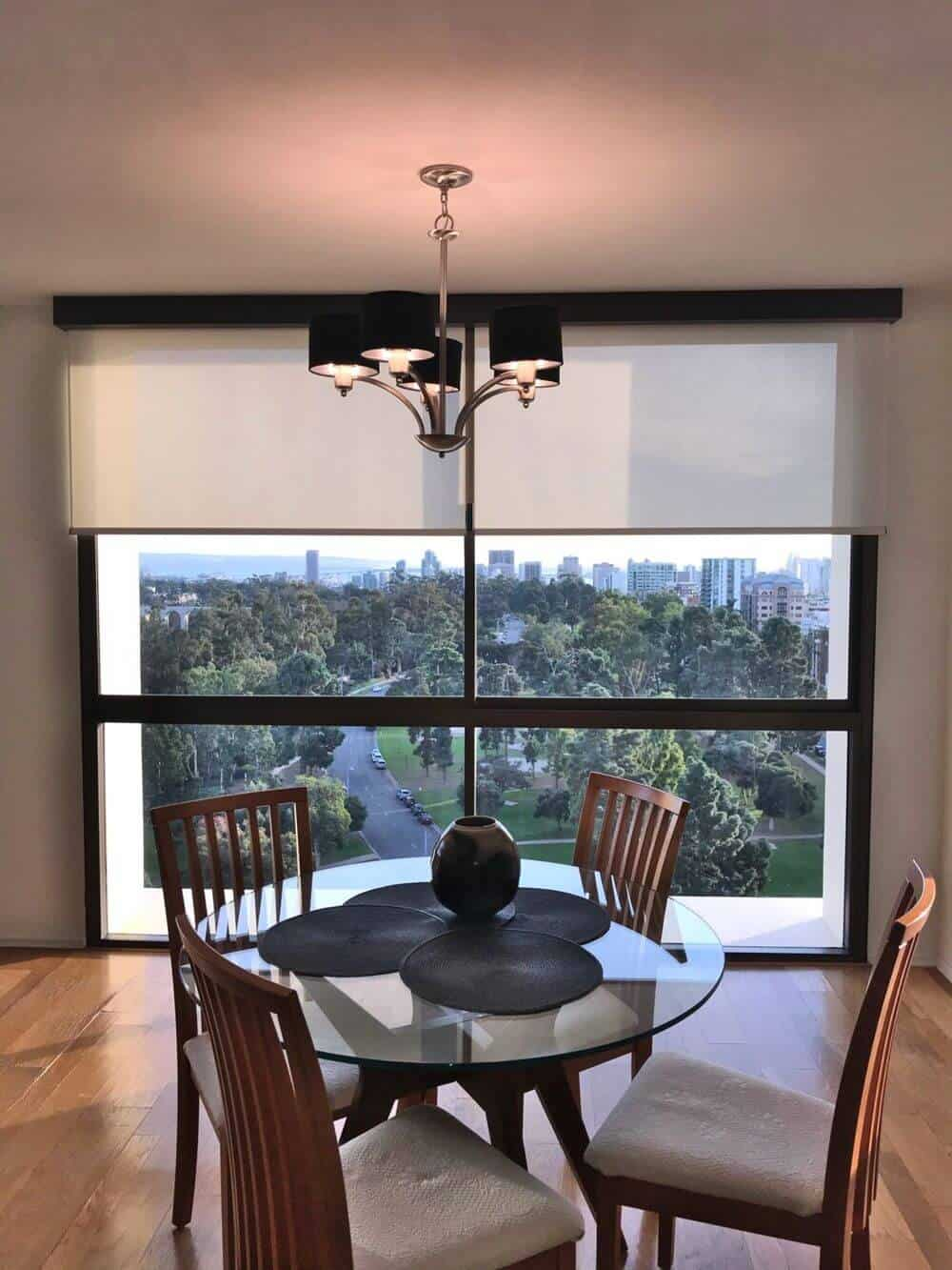 A focused look at this home's round dining nook set lighted by a gorgeous chandelier and is set near the home's glass windows with a solar shade.