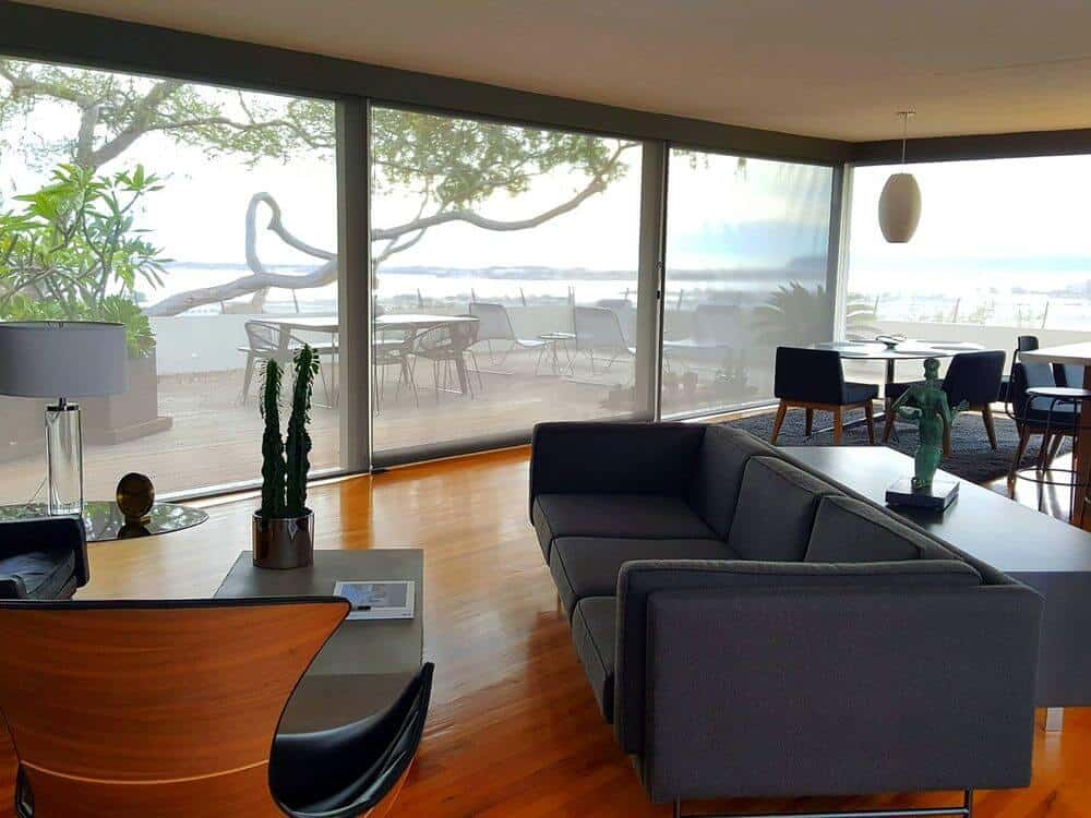 A contemporary living space featuring a modern sofa set that looks absolutely stylish, along with a center table that looks perfect with the living set. The room boasts large glass windows with solar shades.