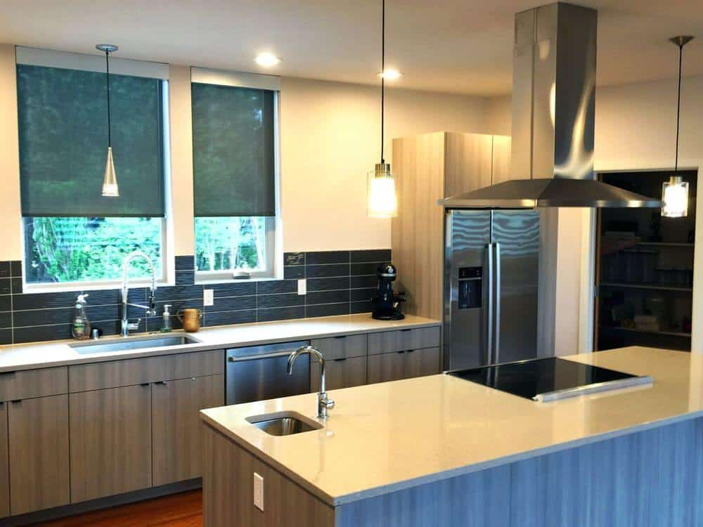 This kitchen features a single wall kitchen counter style and a center island lighted by pendant lights. The room features beige walls and a regular ceiling, along with hardwood flooring.