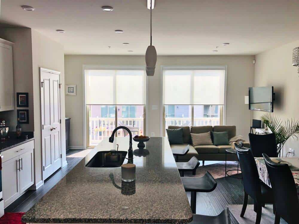 A great room featuring a modern living space with a TV on the wall, a gorgeous dining table and chairs set and a kitchen featuring a granite top center island lighted by pendant lights.