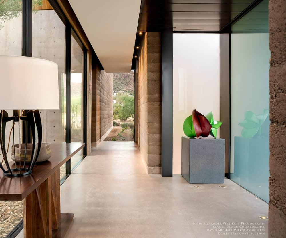Southwestern style foyer featuring floor-to-ceiling glass window walls and a tall ceiling.