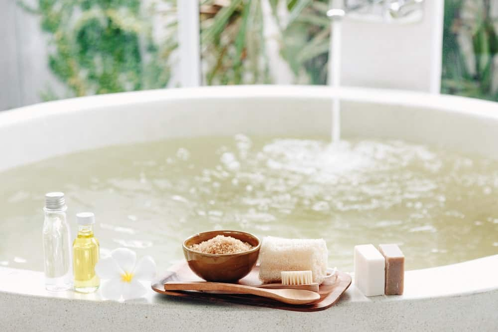 Water fills the bathtub with spa accessories on the side.