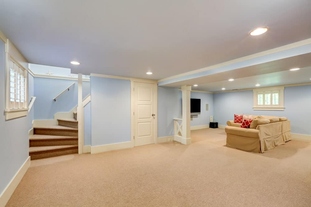A spacious basement with pastel blue walls and beige carpet flooring. It offers a nice brown sofa set and a TV on the wall.