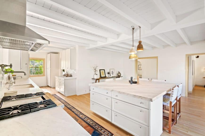 Spacious kitchen featuring a white ceiling with beams and hardwood flooring. The area has a single wall kitchen counter with a white marble countertop similar to the square center island with a breakfast bar.