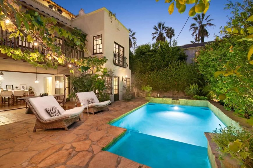 A gorgeous Mediterranean-style swimming pool is focused on this view of this Spanish style mansion's outdoor area.