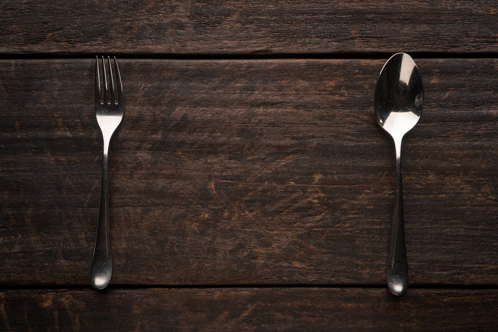 Fork and spoon on wooden background.