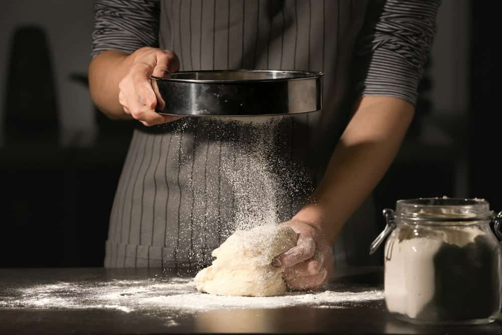 A look at a pastry chef doing his craft, using tamis strainer.