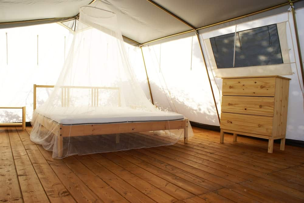 Platform bed with canopy in a luxury tent.