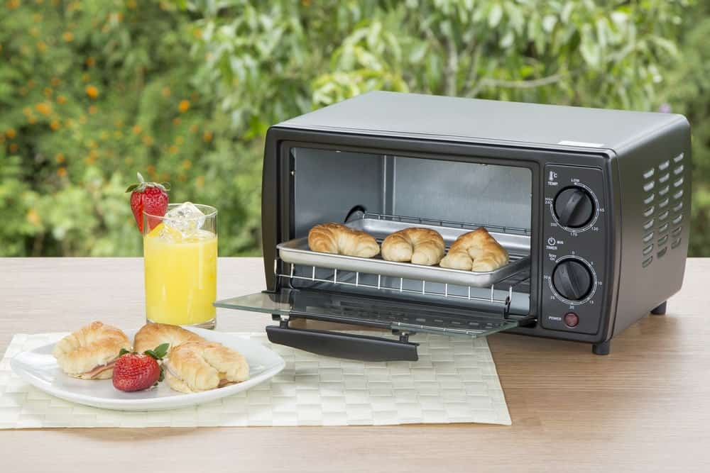 An open toaster oven with croissants beside on an outdoor breakfast setup.