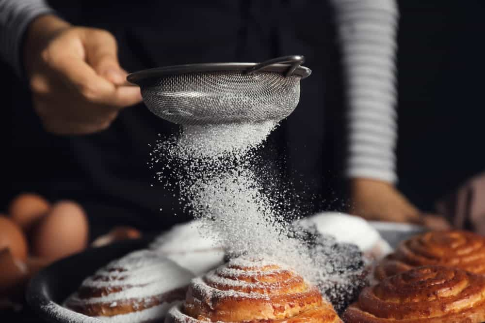 This one is a traditional strainer. A pastry chef is using it in this photo during the preparation of his bread.