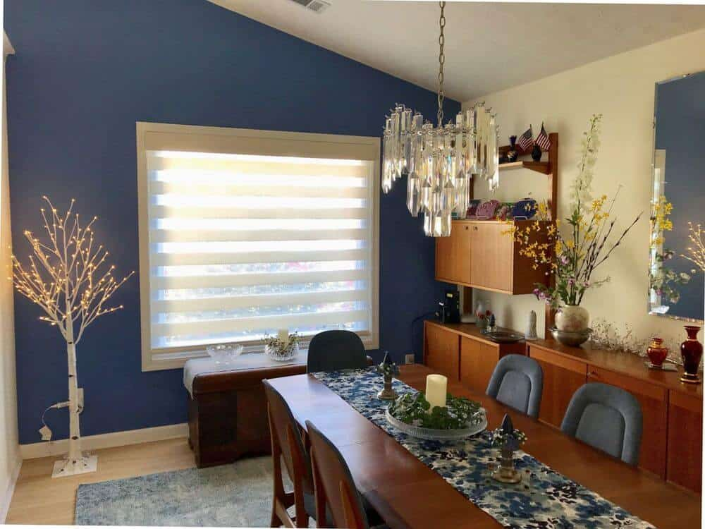 Dining room featuring a wooden dining table set lighted by a luxurious chandelier and is set on top of an area rug. The area features a blue wall and a shed ceiling, along with a glass window featuring a transitional window shade.
