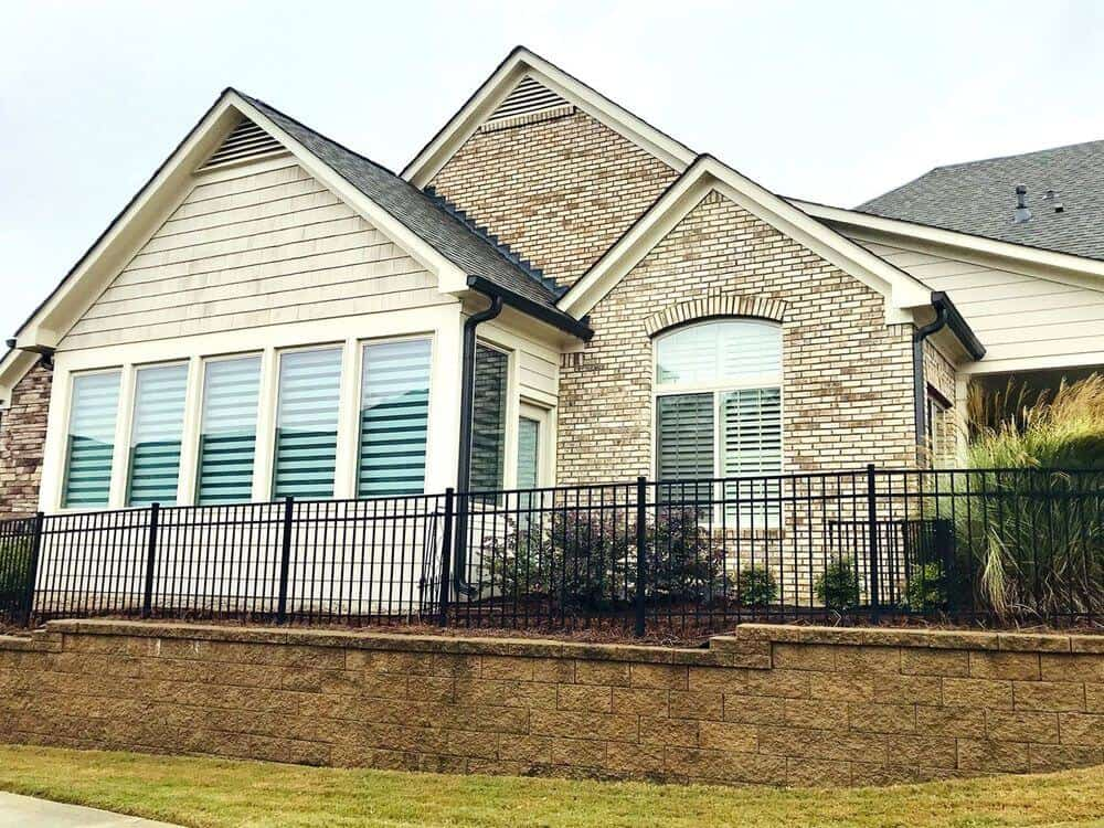A view of this house's gorgeous exterior and glass windows featuring transitional window shades.
