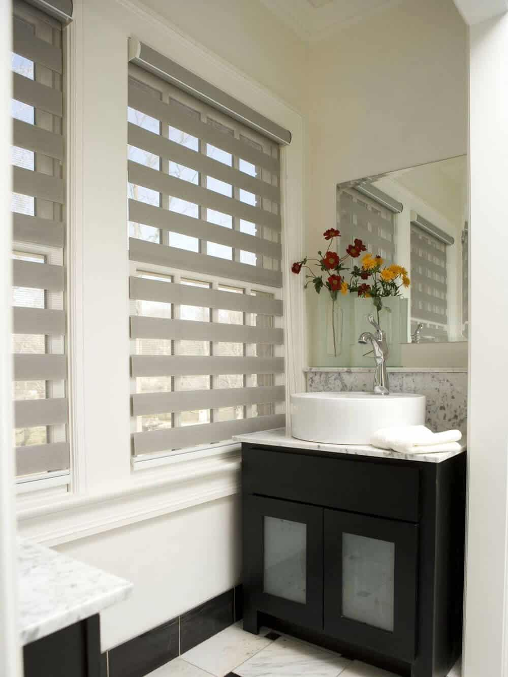 A primary bathroom offering two sink counters, both featuring marble countertops and large vessel sinks. The room has a tall ceiling and glass windows featuring transitional window shades.