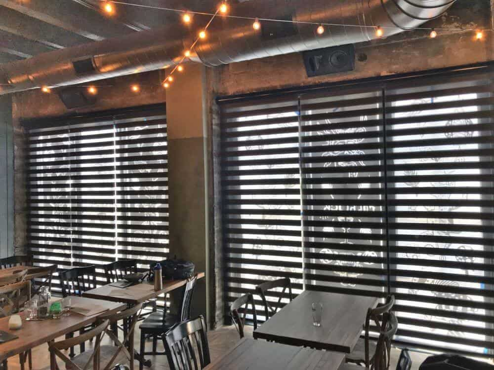 A restaurant boasting large windows with transitional window shades and a tall ceiling with bright warm lighting. The dine-in area also offers multiple dining table set.