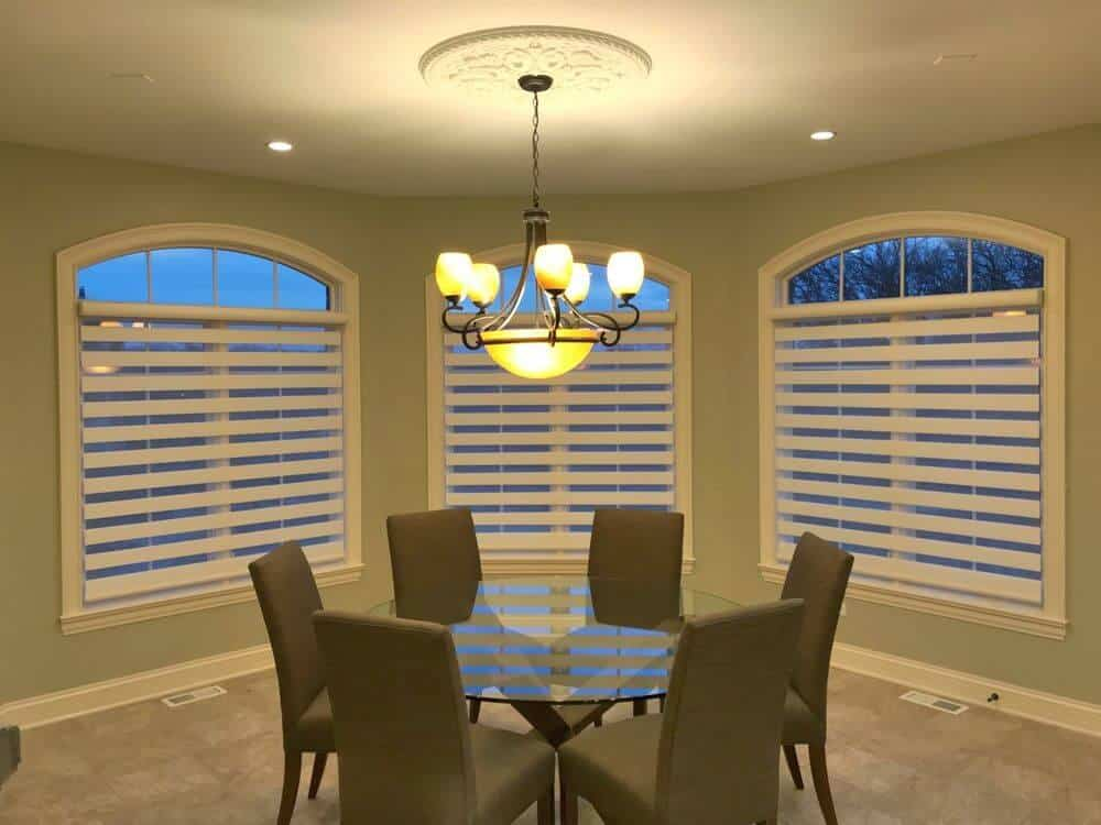 A focused look at this dining room's round glass top dining table set paired with modern gray chairs and is lighted by a charming ceiling light. The windows in the room also feature transitional window shades.