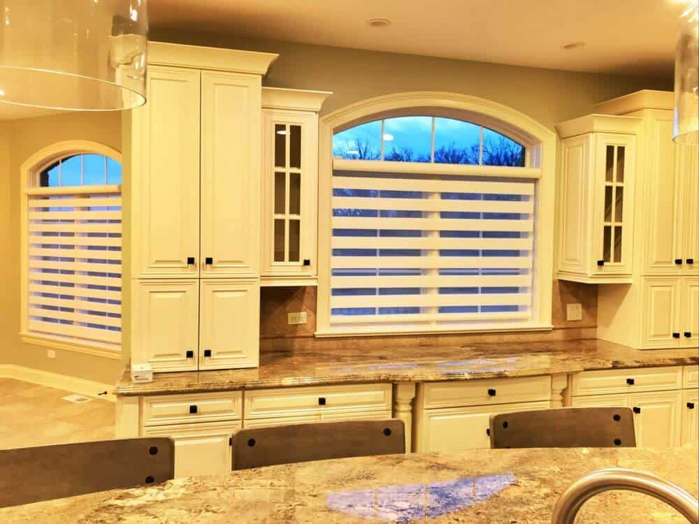 A kitchen boasting marble countertops on both kitchen counters and center island. The island also offers space for a breakfast bar. There are windows featuring transitional window shades.