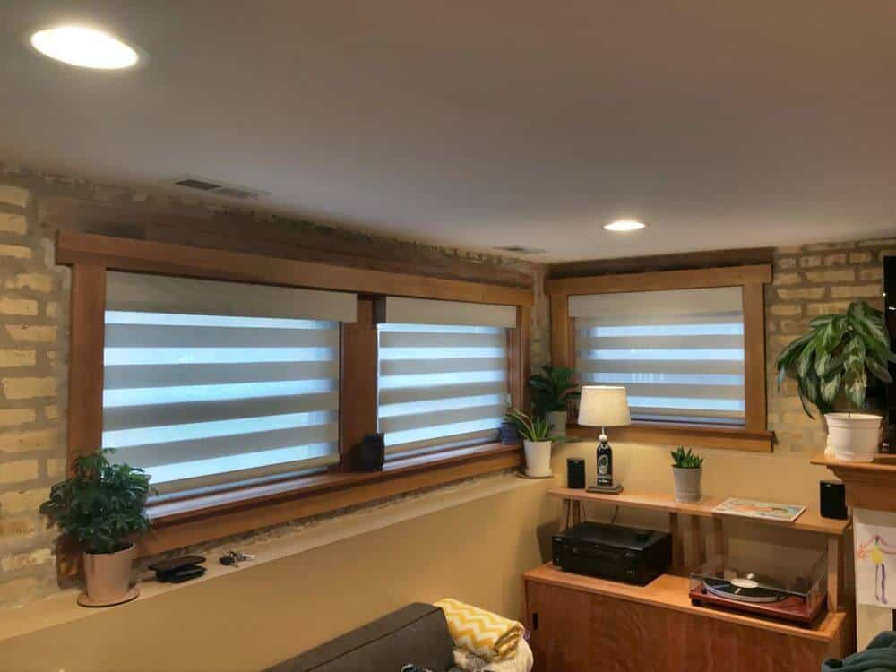 This room boasts stylish brick walls along with glass windows featuring transitional window shades. The room also has a regular ceiling with recessed ceiling lights.