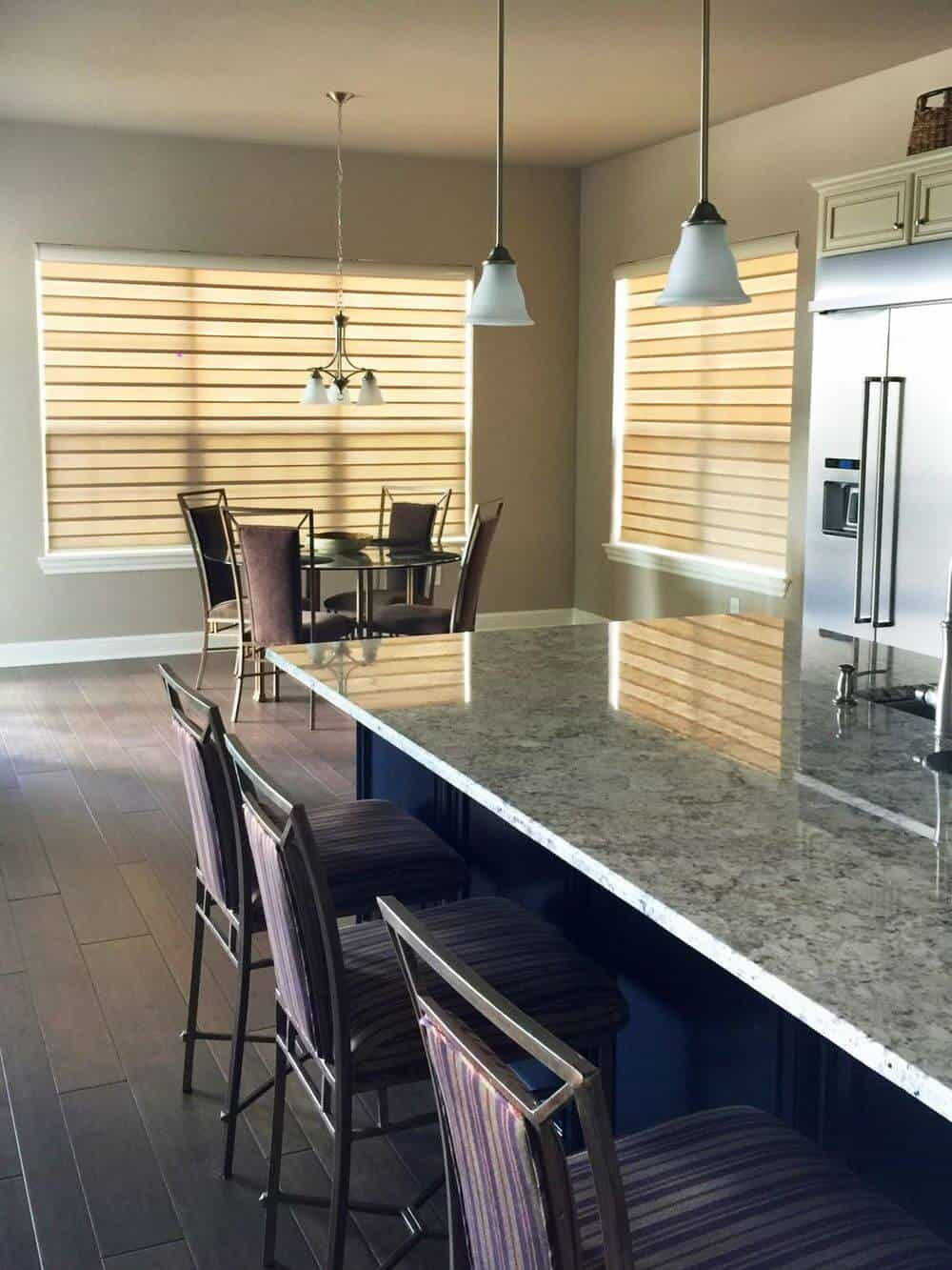A dine-in kitchen featuring light gray walls and hardwood floors. There's a round dining nook on the side while the kitchen offers a large center island with a breakfast bar.
