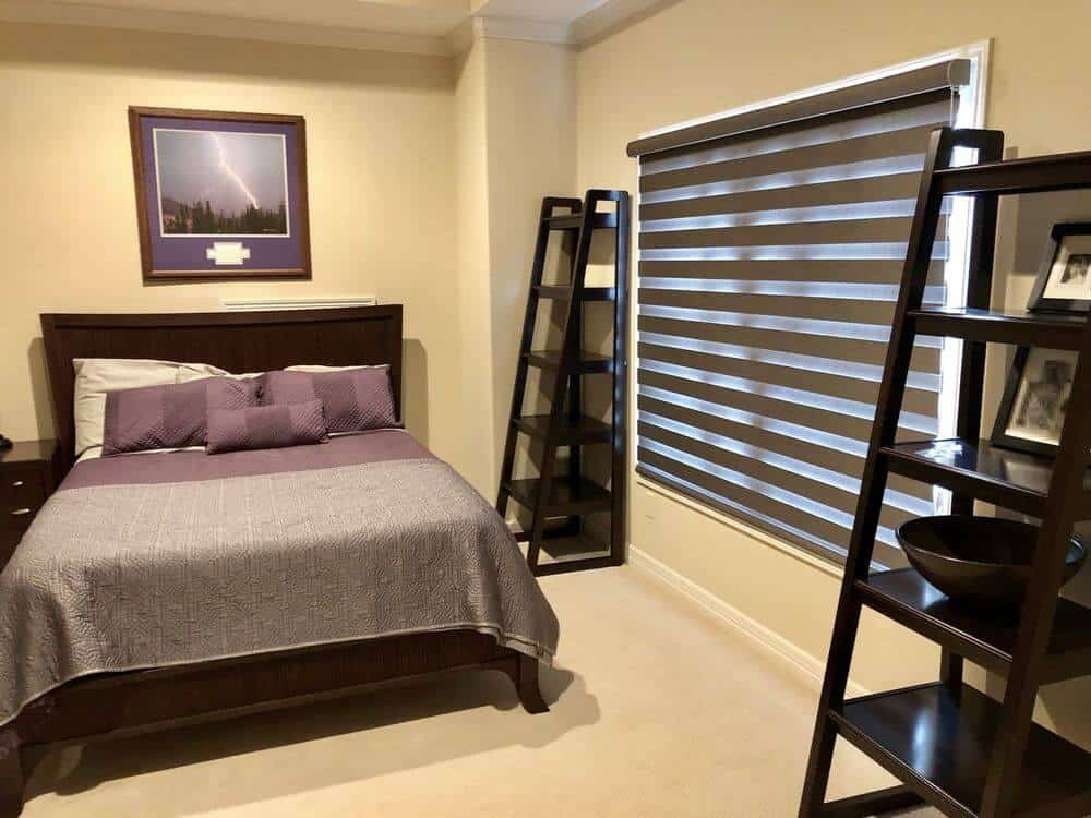 A guest bedroom featuring a comfy bed with two stylish ladder-style freestanding shelves. The room features carpet flooring and beige walls.