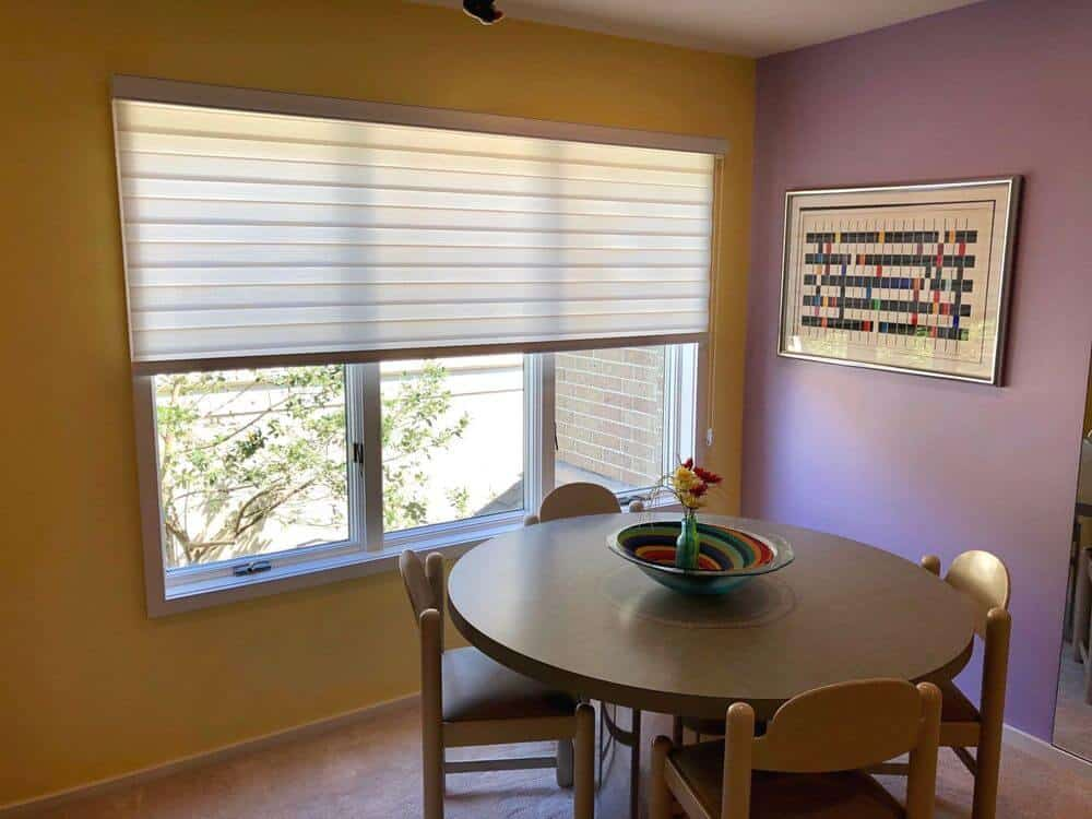 A simple dining area featuring a brown round dining nook for four surrounded by yellow and purple walls. The dining table is set near the glass windows featuring transitional window shades.