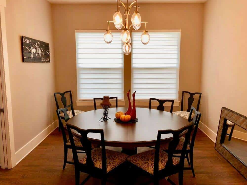 A dining room boasting a classy dining table and chairs set lighted by a stunning ceiling light. The room has two small windows featuring transitional window shades.