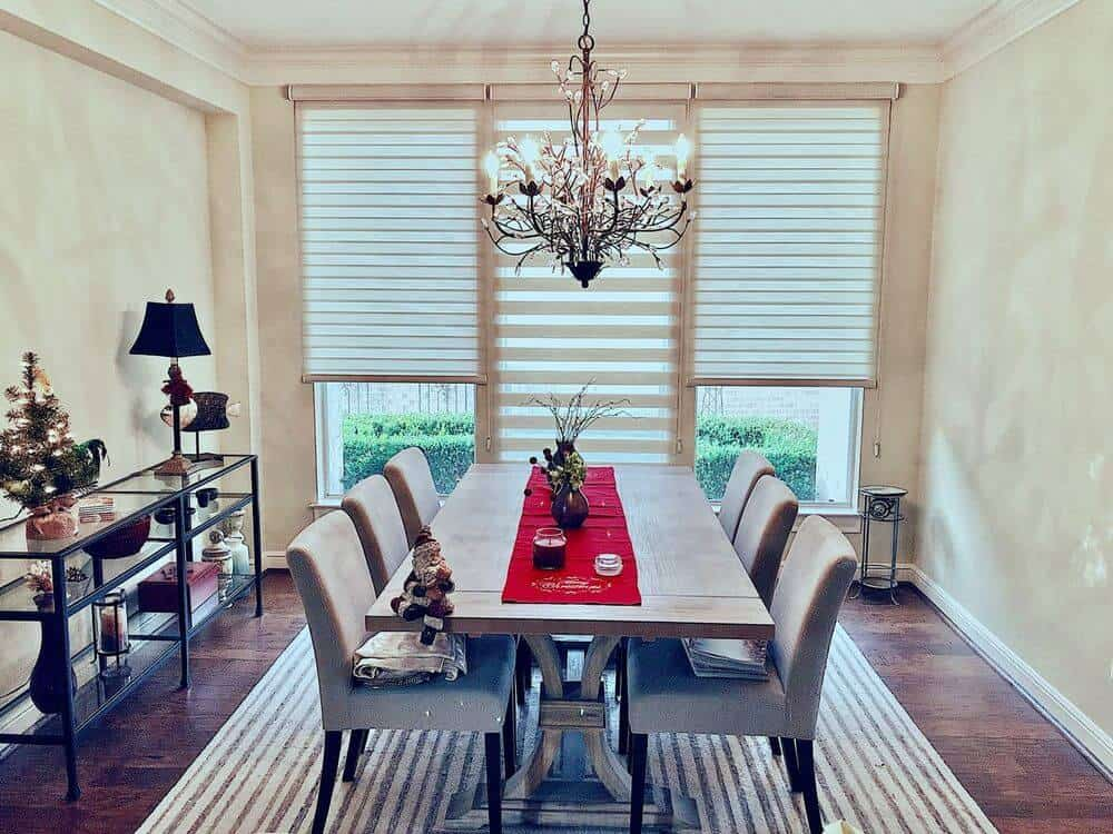 Dining room boasting an elegant dining table and chairs set on top of a stylish area rug covering the hardwood flooring. The room is lighted by a luxurious chandelier.