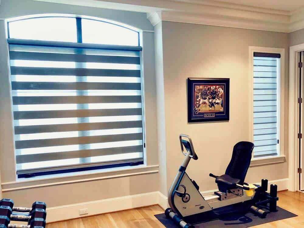 A home gym featuring light gray walls and hardwood floors, along with a white ceiling. The room also features windows with transitional shades.