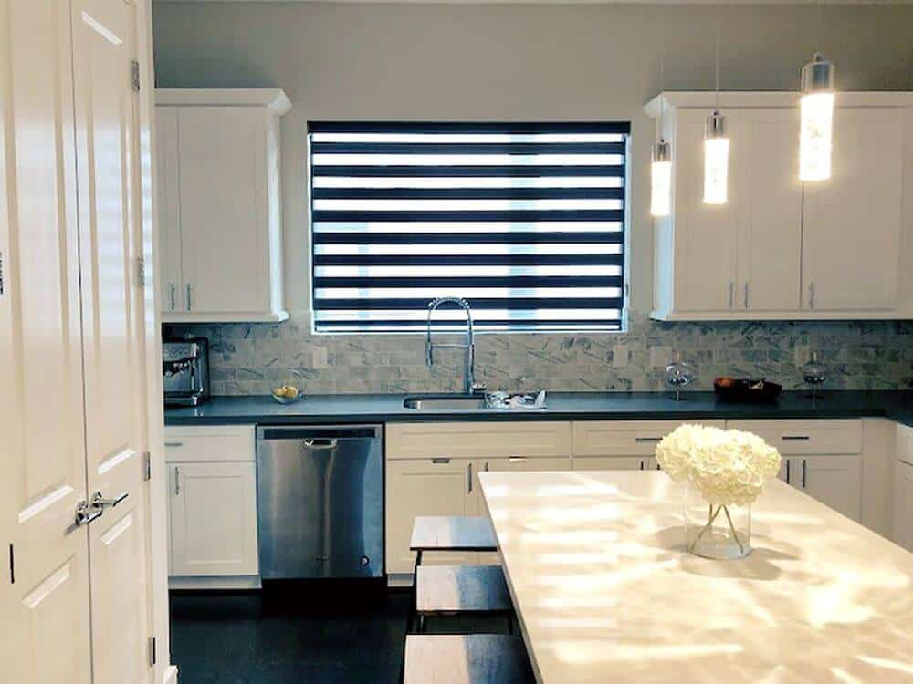 A dine-in kitchen featuring an L-shaped kitchen counter with a black countertop. There's a center island with a breakfast bar as well, lighted by pendant lights.