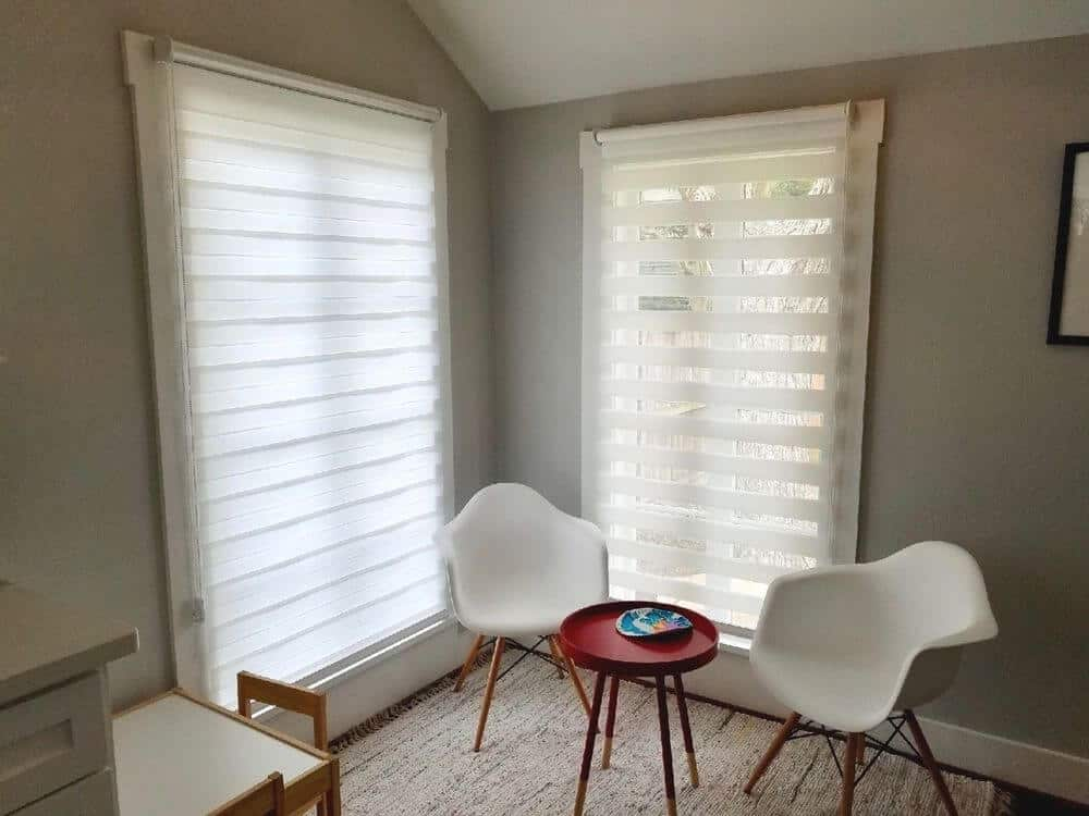 A sitting area on the side set near the windows with transitional window shades. The home features light gray walls and hardwood floors.