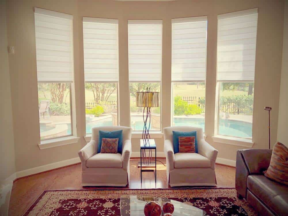 Living space featuring a classy sofa set and a stylish area rug where the glass top center table is set. The home has beige walls and vertical windows featuring transitional window shades.