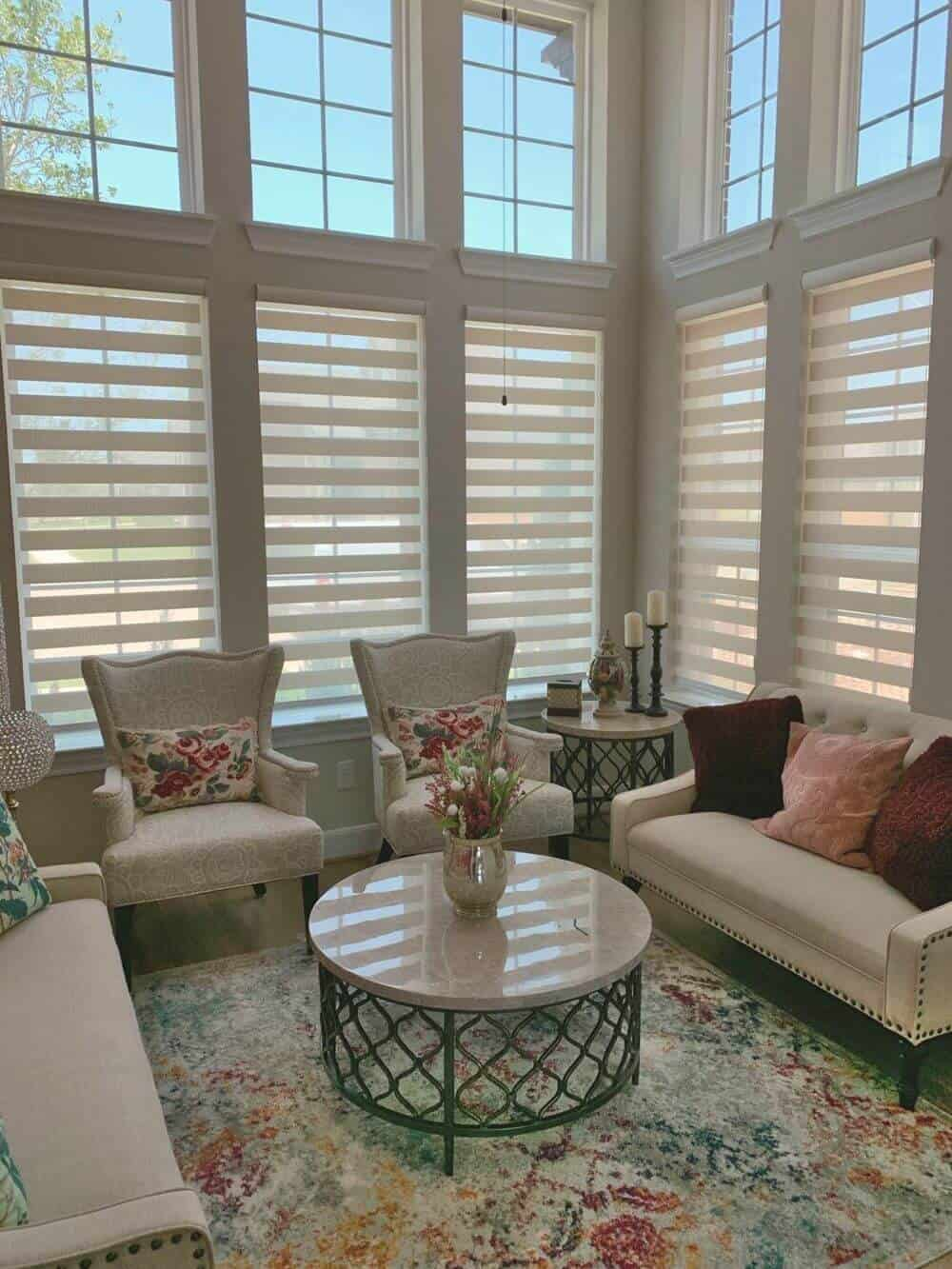 A living space featuring a classy sofa set and a gorgeous center table on top of an area rug covering the hardwood flooring. The home has a tall ceiling and windows with transitional shades.