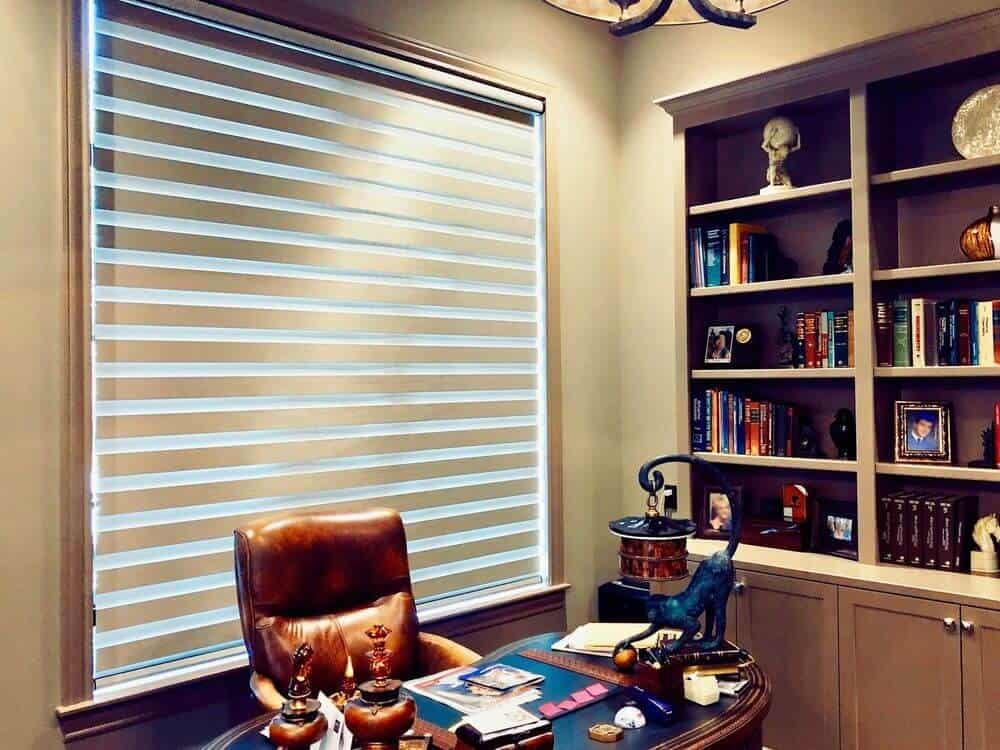 A home office boasting an elegant office desk and chair set along with built-in shelving on the side with cabinetry. The ceiling light looks absolutely attractive as well.