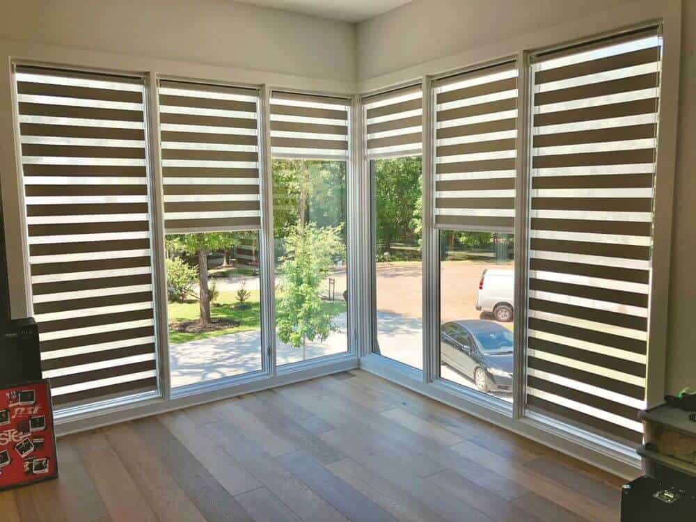 A focused look at this home's glass windows featuring transitional window shades. The home also has hardwood floors.