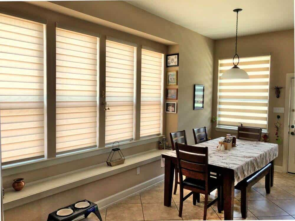 A dining room featuring beige tiles flooring and walls, along with windows featuring transitional window shades. The area features a wooden dining table and chairs set.