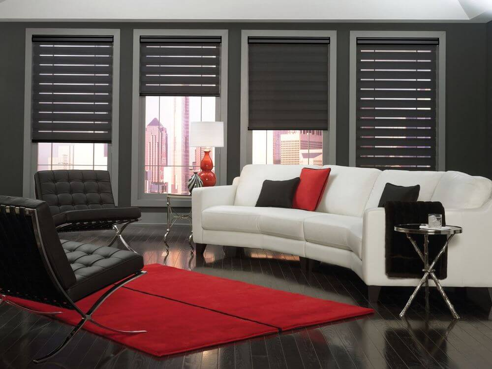 Contemporary living room featuring dark hardwood floors, dark gray walls and a white ceiling. The room offers a white curved couch and a pair of modern seats, along with a red area rug.