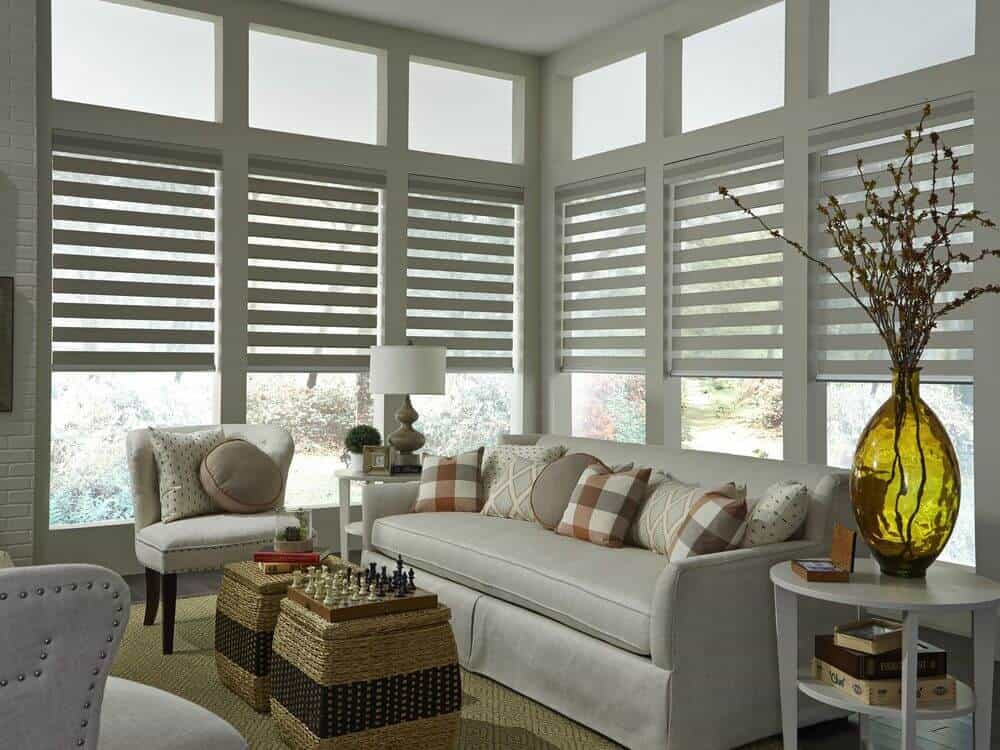 Living room boasting a set of gray seat. The area features a brown area rug covering the hardwood flooring along with glass windows with transitional window shades.