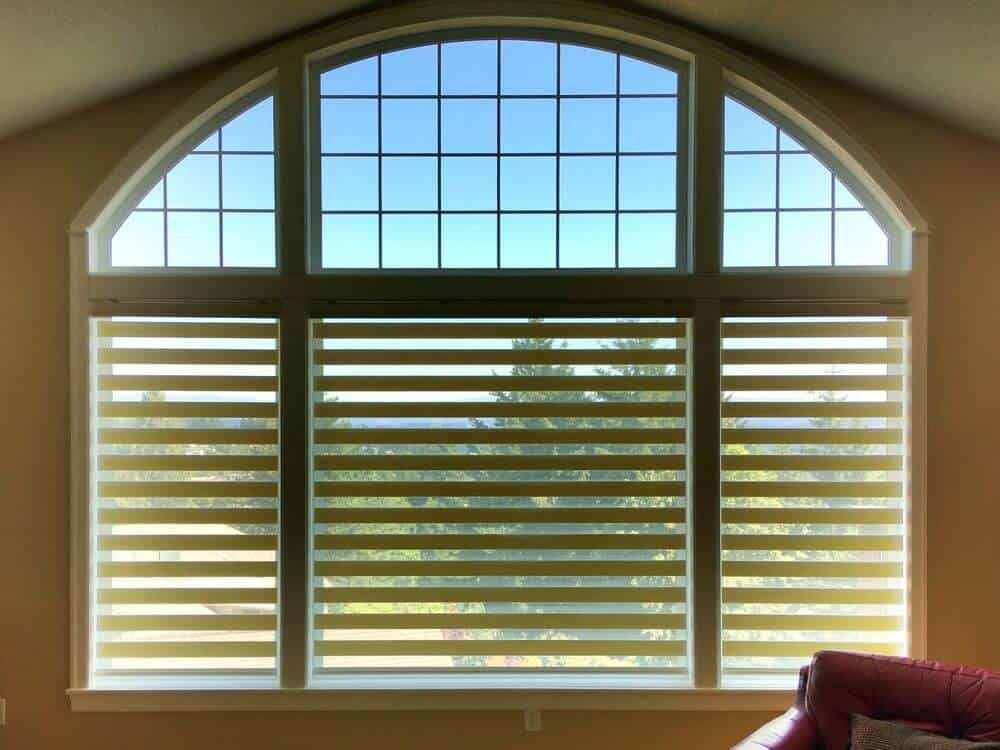 A focused look at this home's large window featuring a transitional-style window shade.