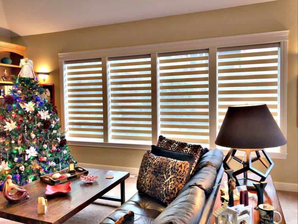 This living space boasts an elegant leather sofa set and a wooden center table along with a Christmas tree decoration on the side. The home's windows feature transitional shades.