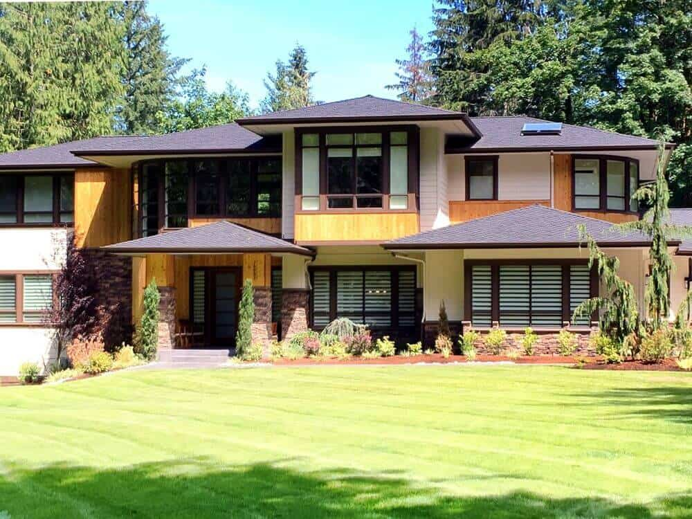 A look at this house's beautiful exterior with glass windows featuring window shades. The home's outdoor features well-maintained lawn area and beautiful garden.