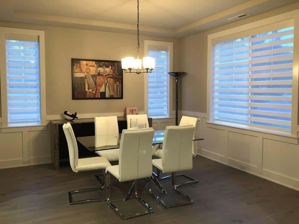 A spacious dining area boasting a glass top dining table paired with modern white chairs, lighted by a charming ceiling light. The room features light gray walls, hardwood floors and a tray ceiling.